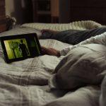 Personne allongée sur un lit regardant une tablette