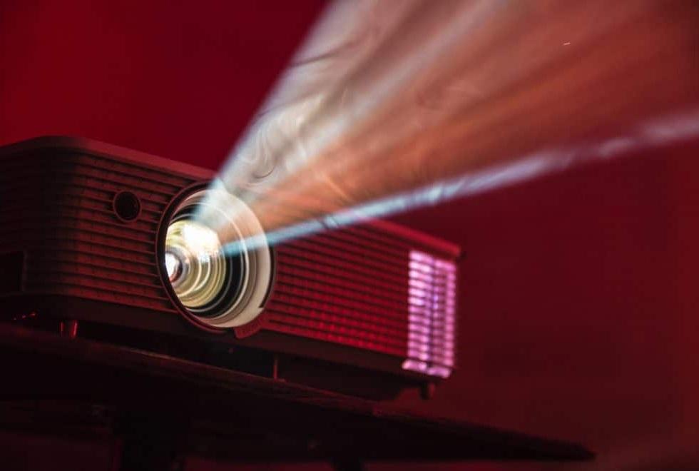 video projecteur allumé lumière blanche sur fond rouge