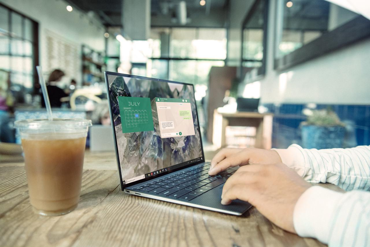 homme sur son ordinateur dans un café avec une boisson